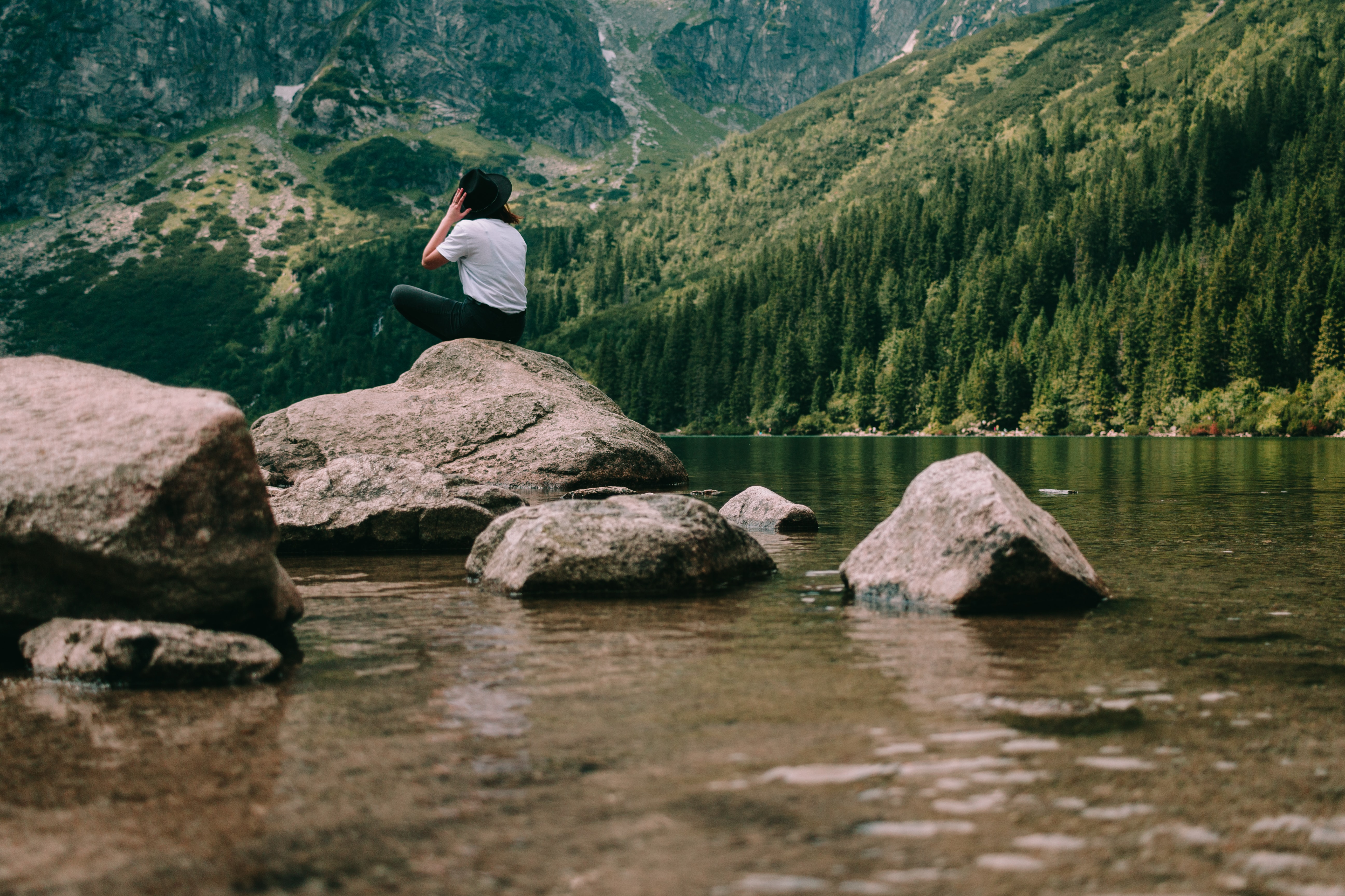person sitting on rock formation facing mountains