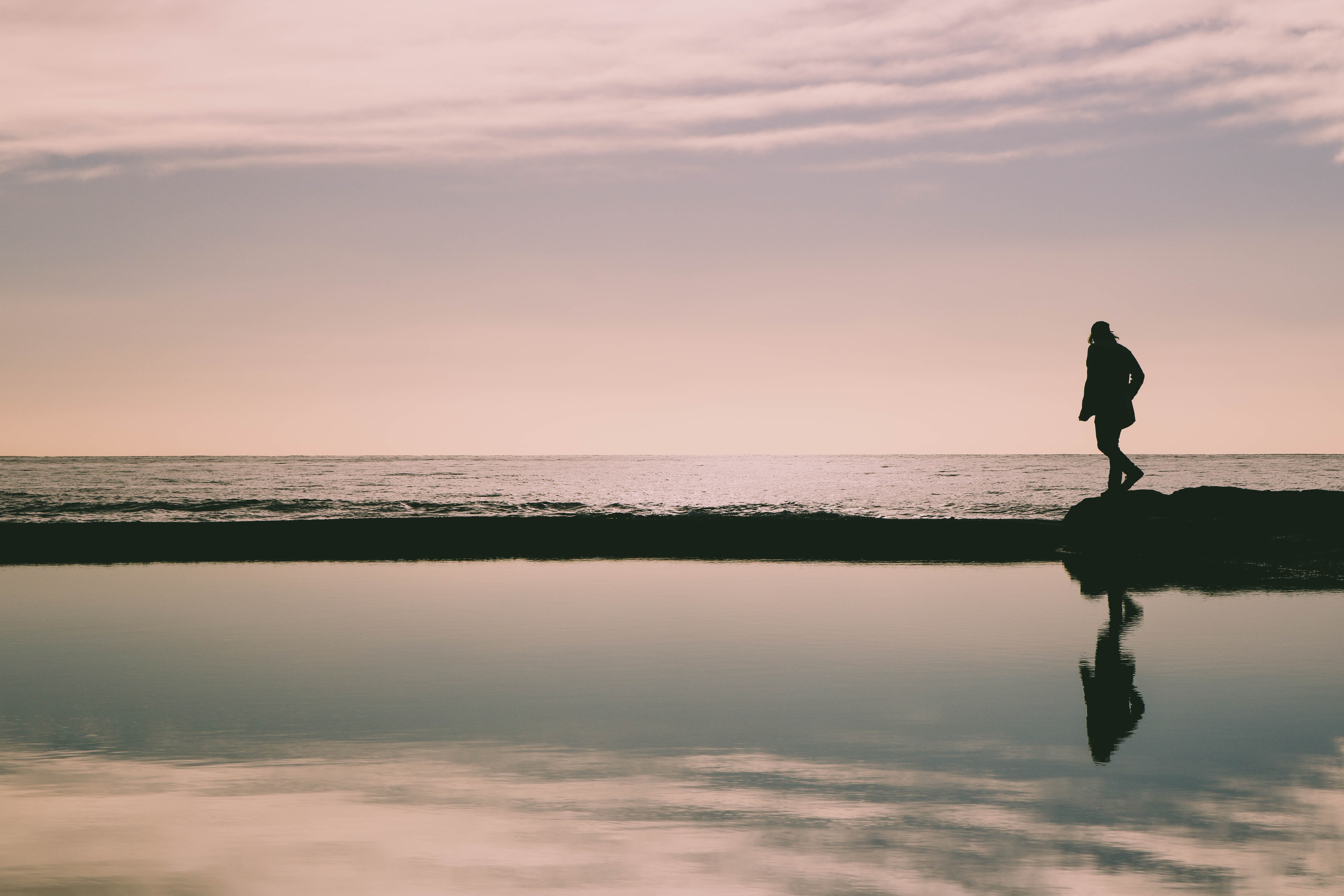 silhouette of woman on rock formation in seashore