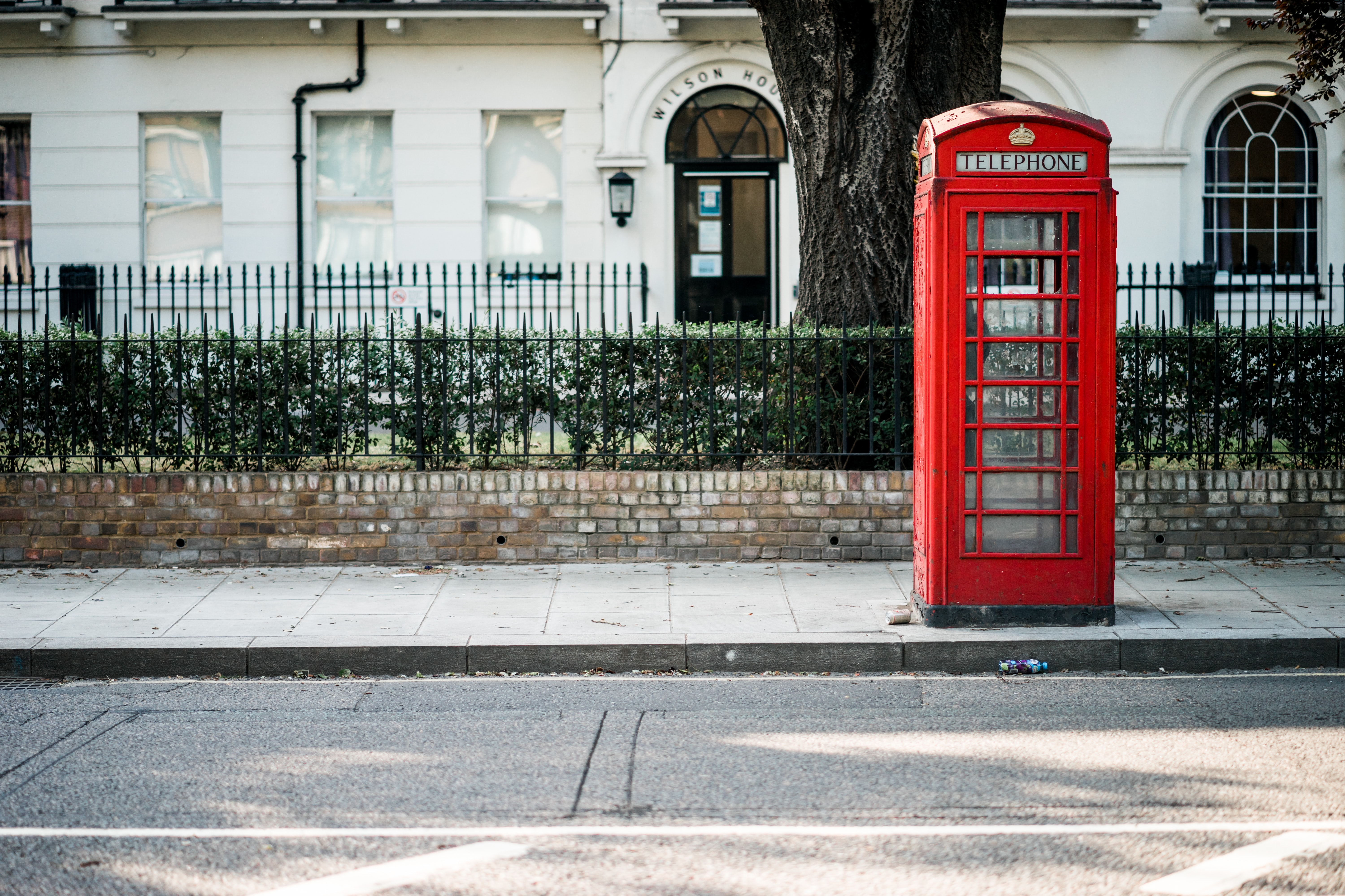 red telephone booth beside road