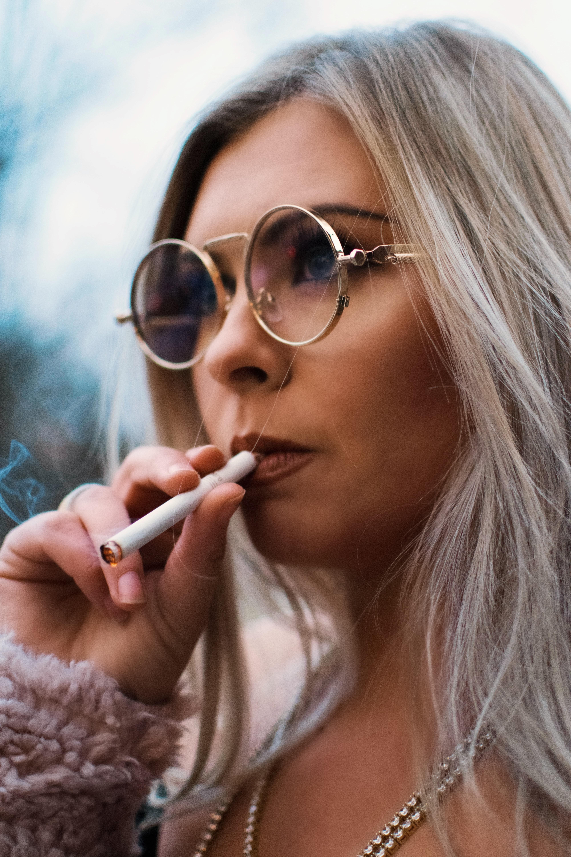 person holding cigarette stick wearing eyeglasses