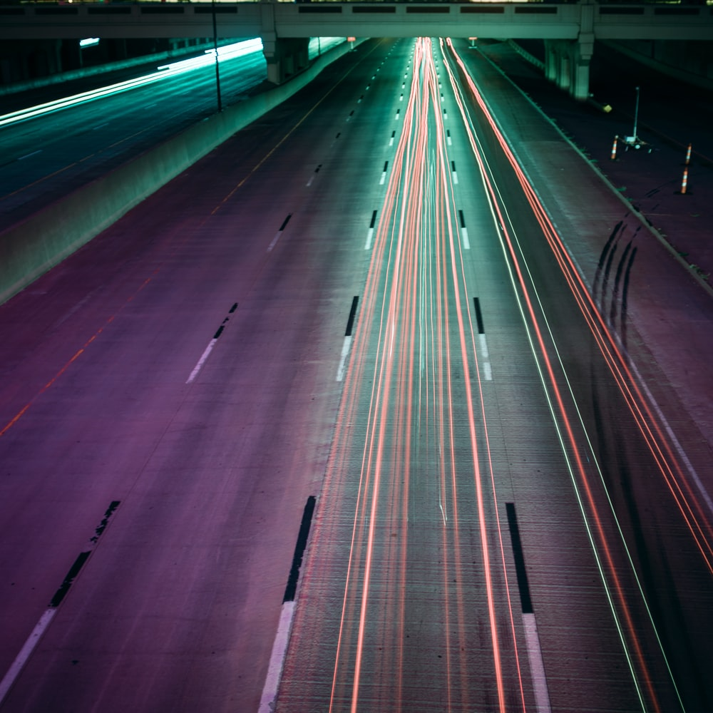 time lapse photography of moving vehicles on road