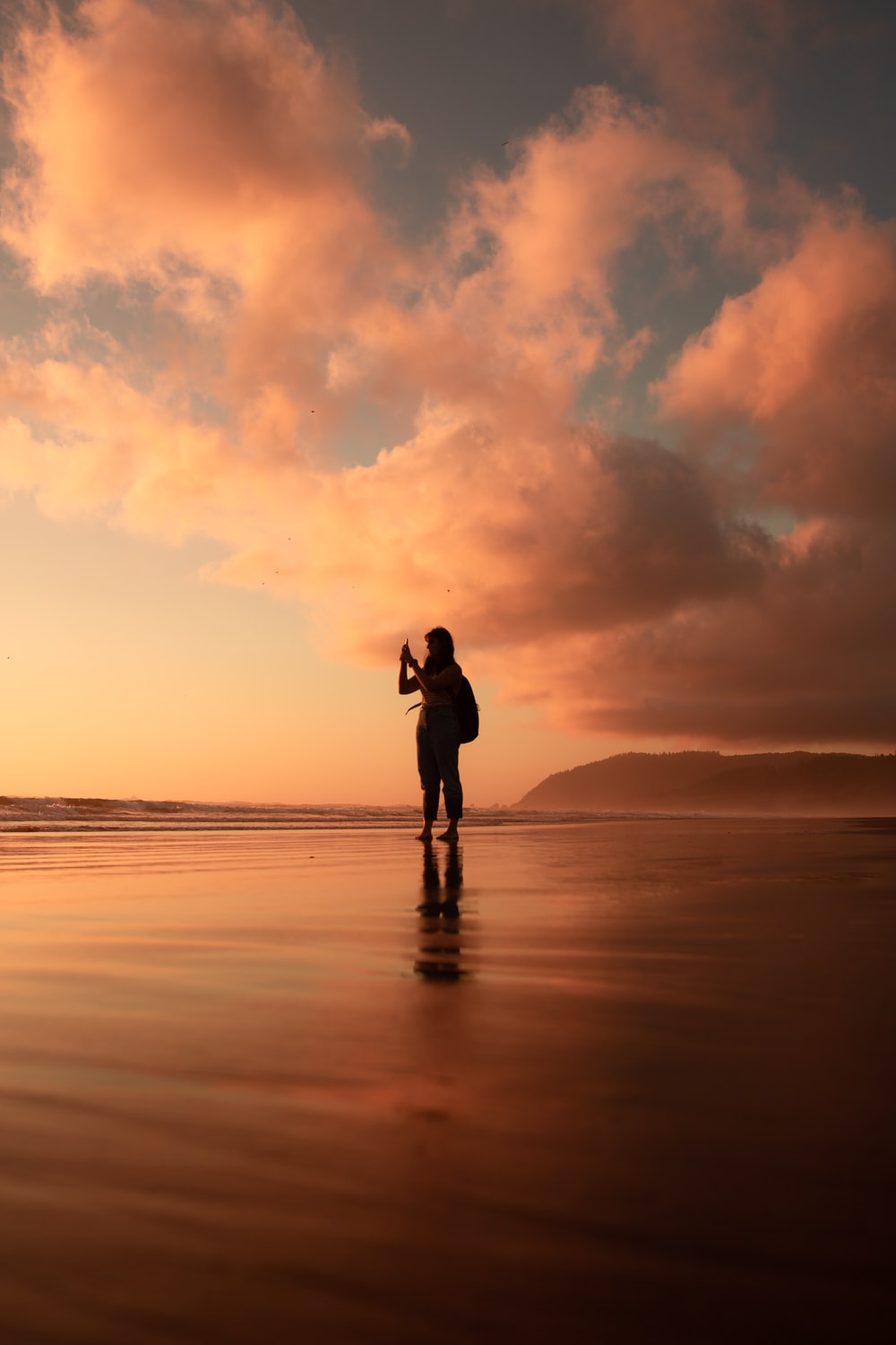 silhouette of woman standing on seashore in golden hour background