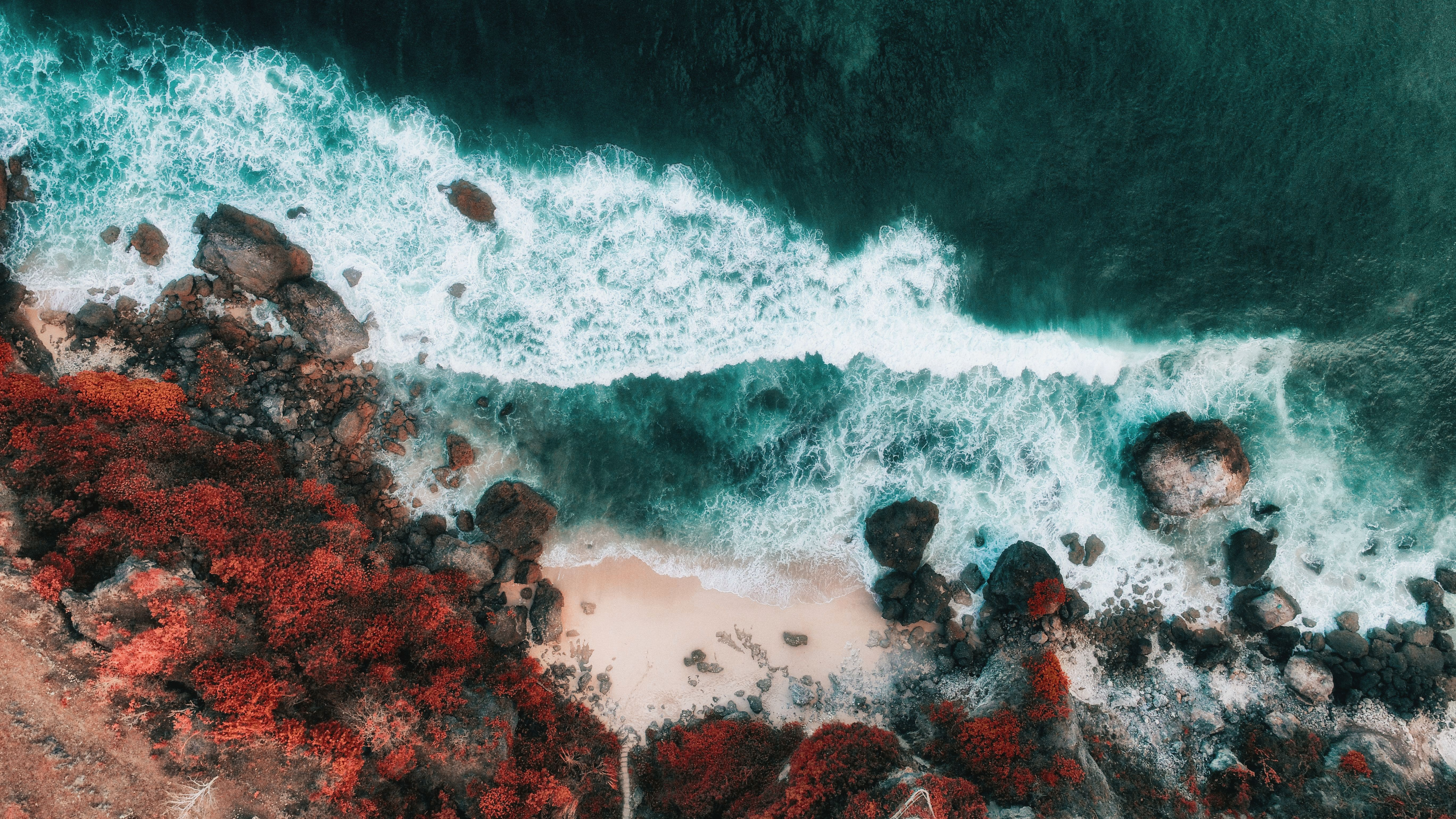 aerial photo of rock formation and sea waves