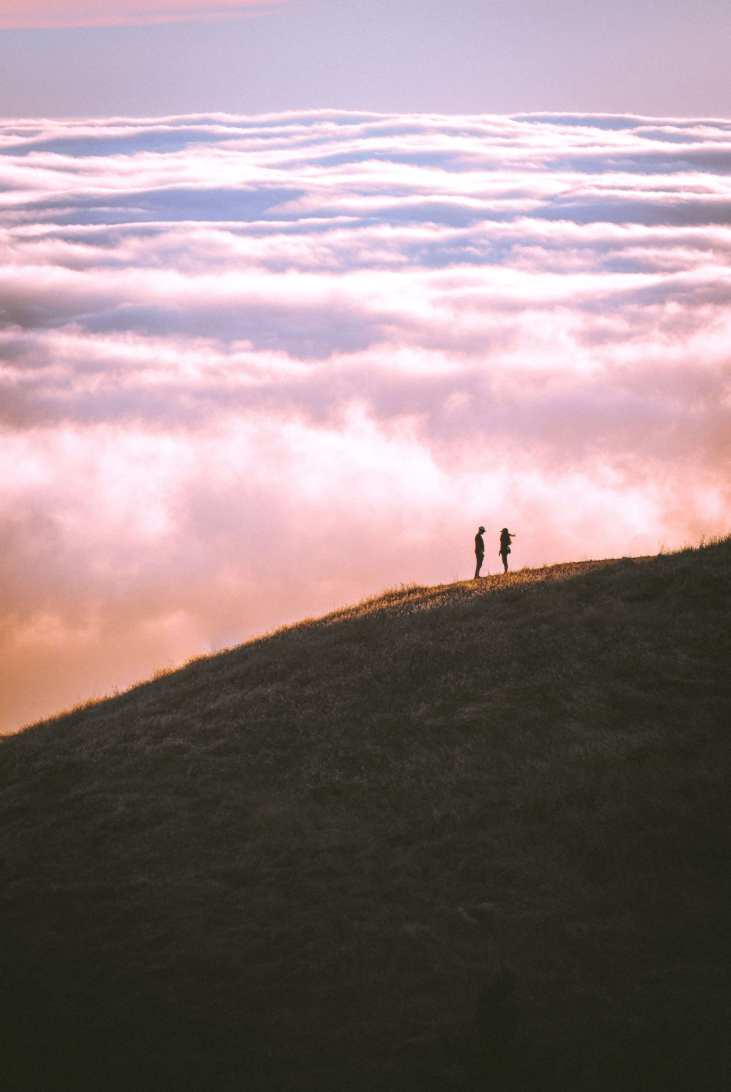 Couple Standing On Grass Field Mountain