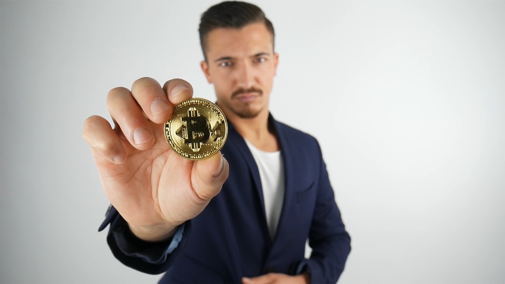 man in dark-blue suit jacket holding gold-colored coin