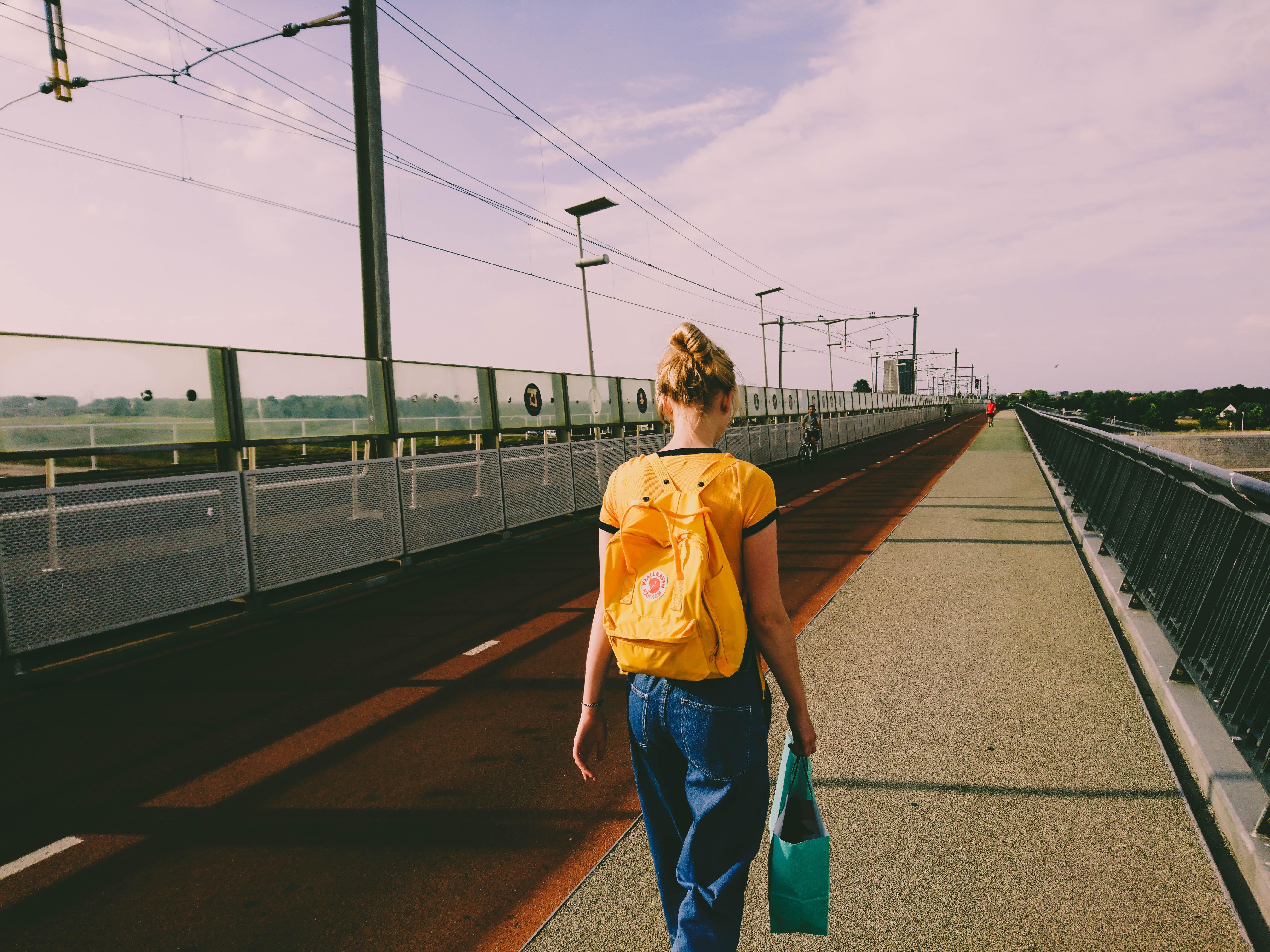woman in yellow walking on street