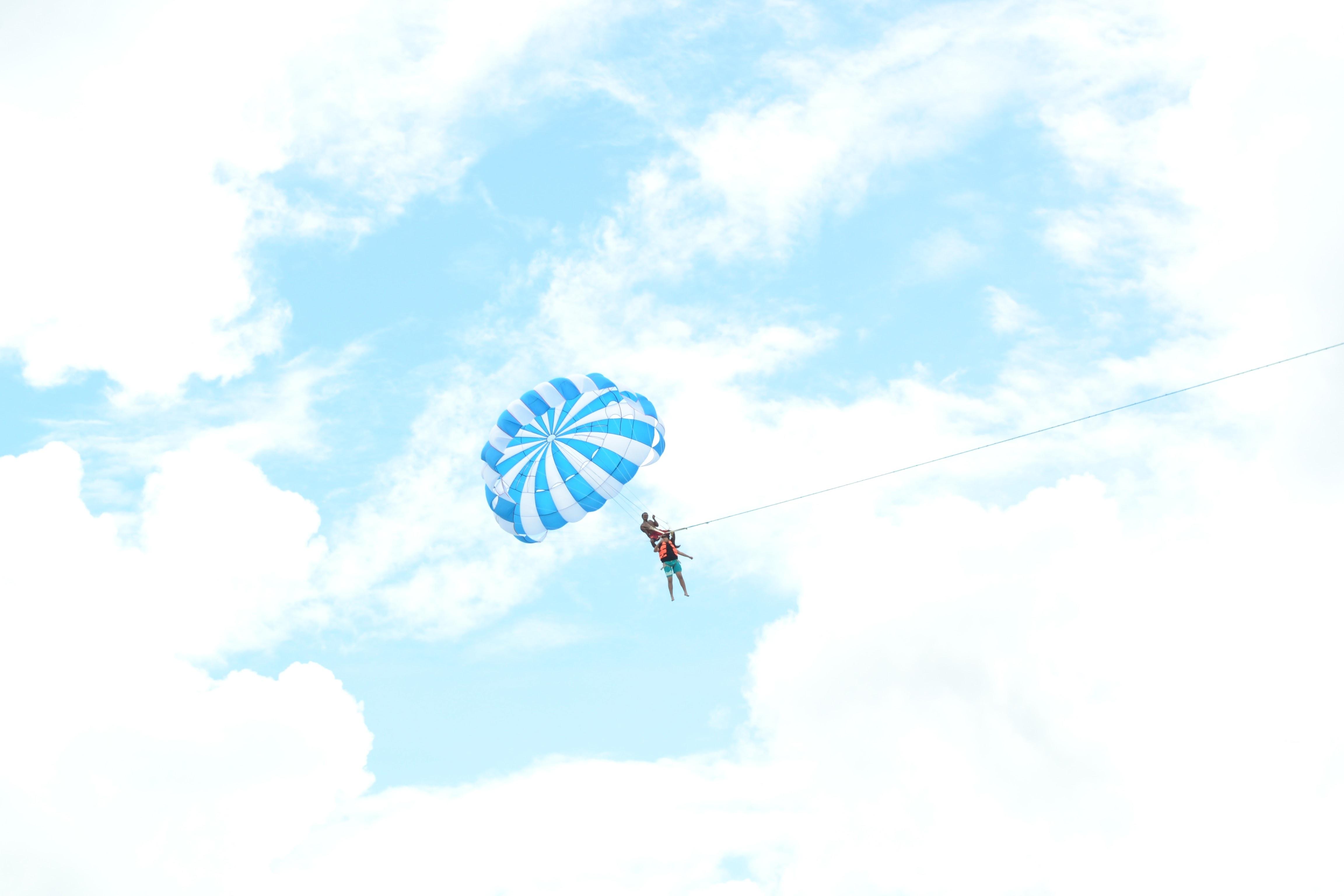 person riding on blue parachute