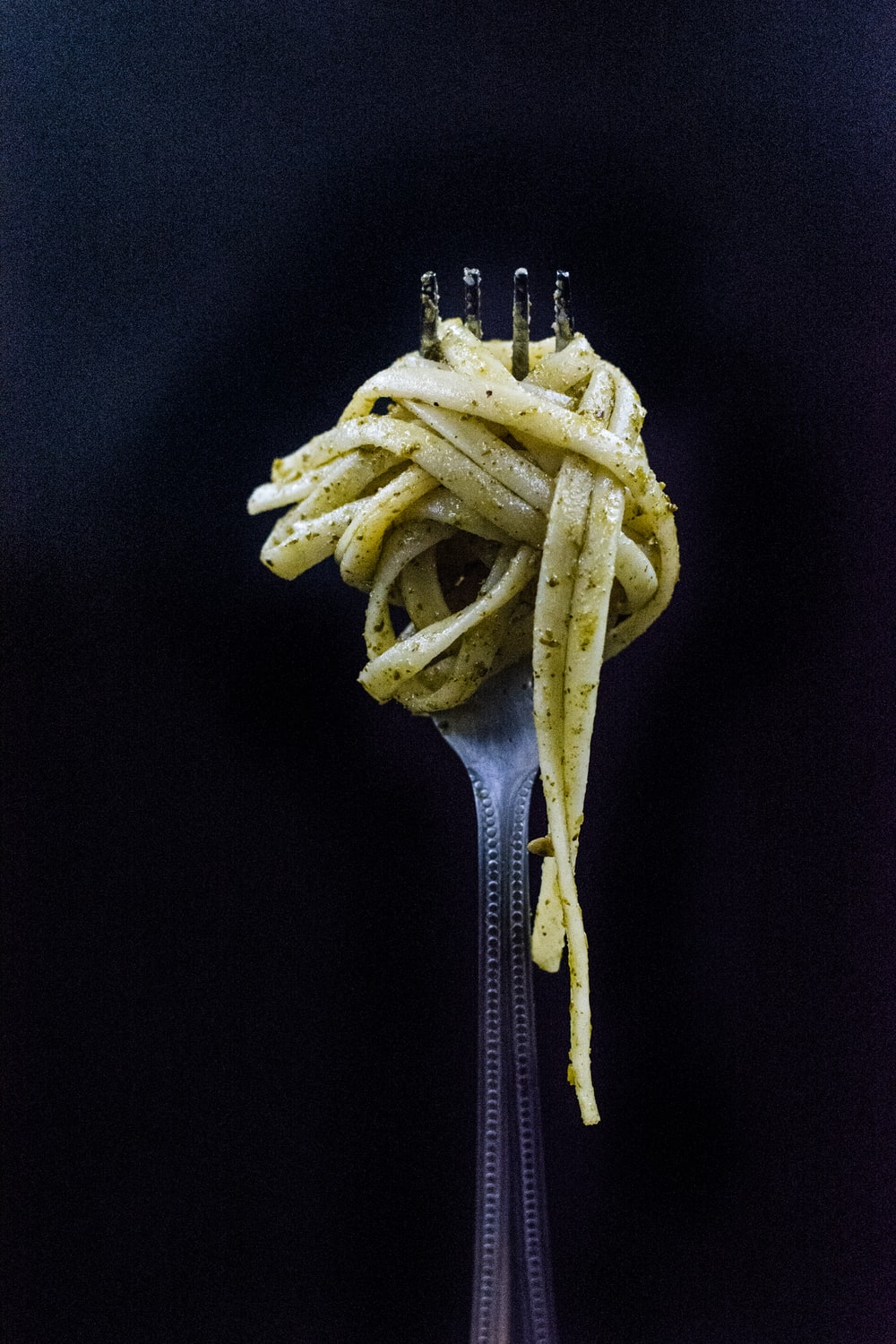 selective focus photography of fork with noodle