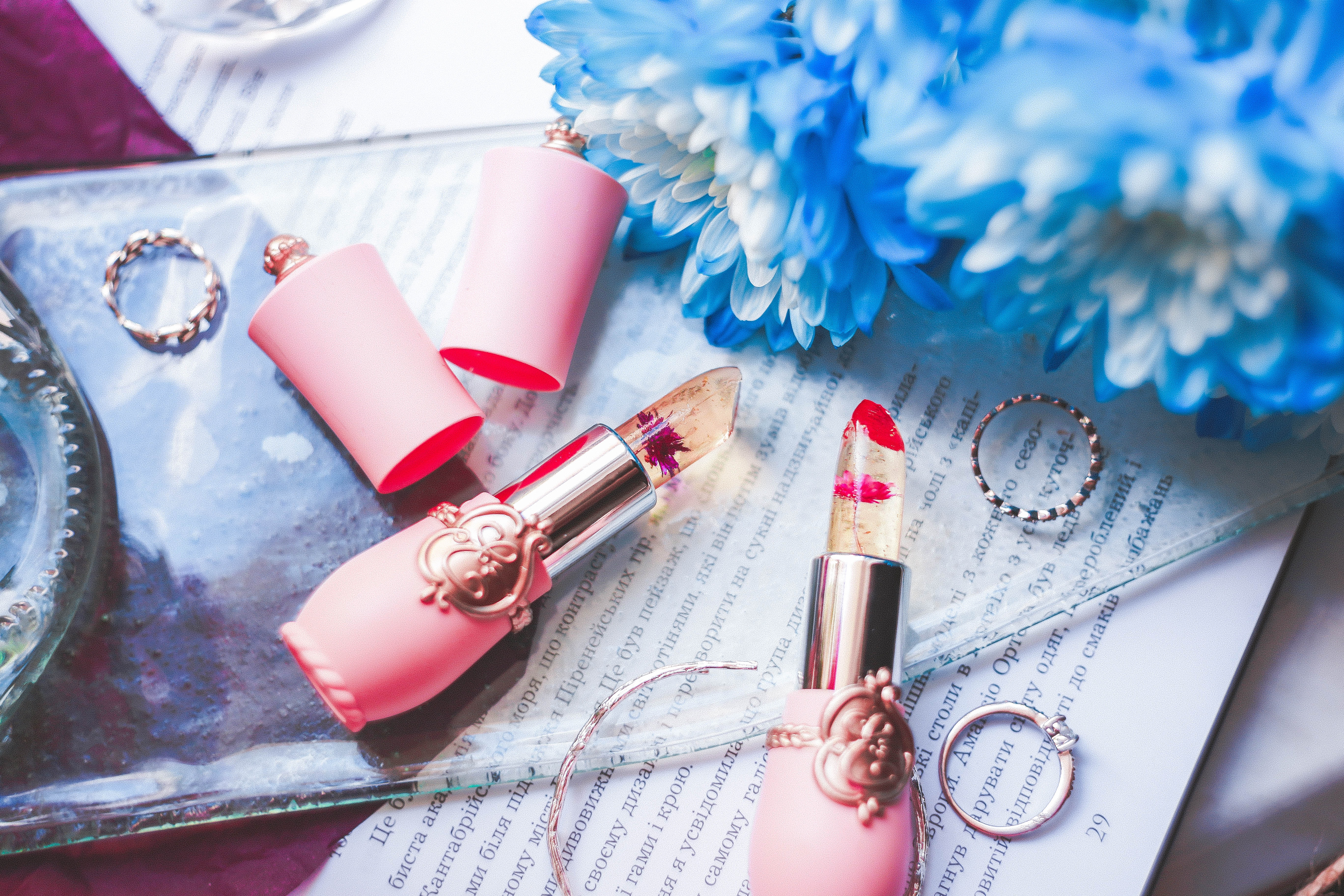 lipsticks beside blue petaled flowers