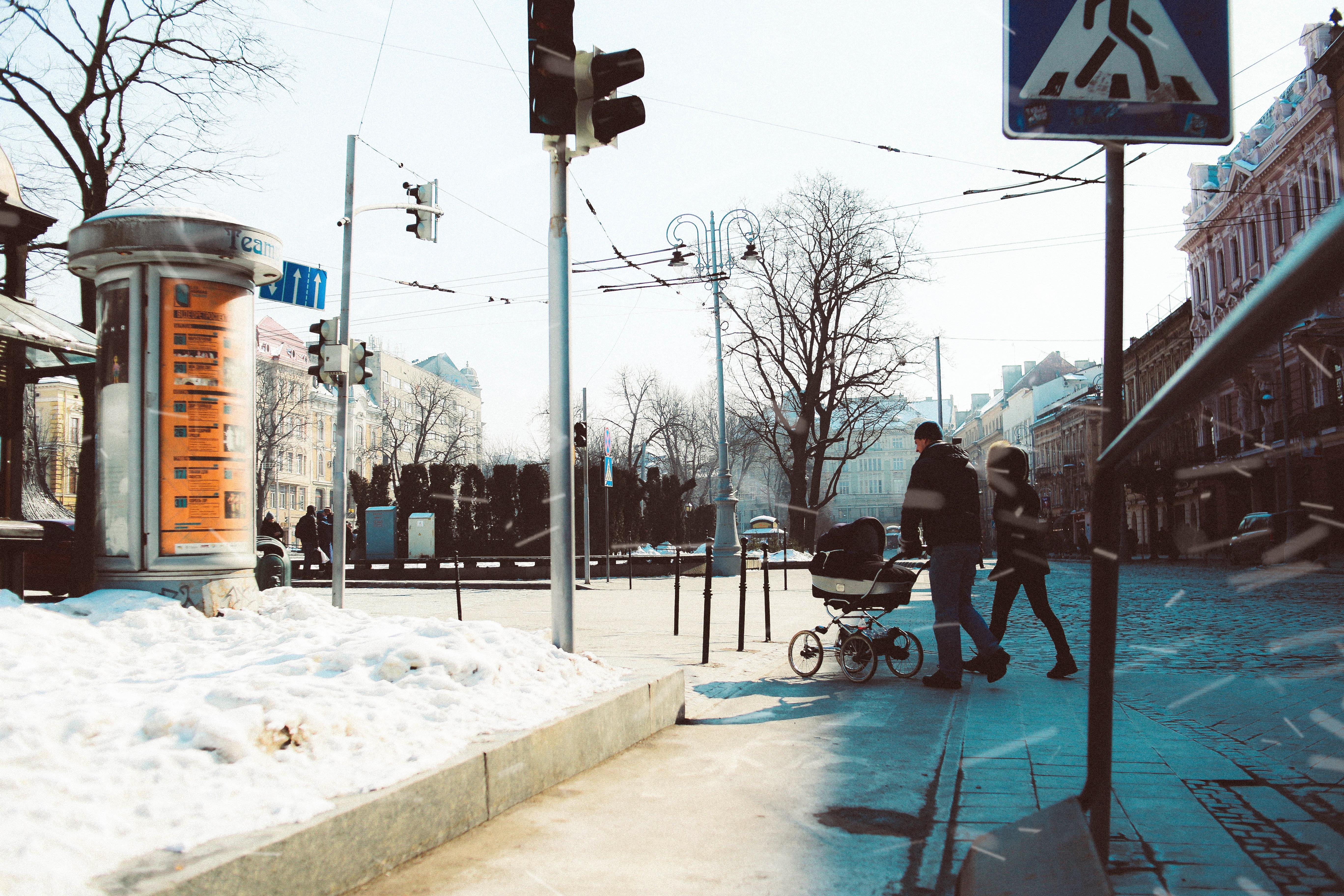 man pushing black stroller