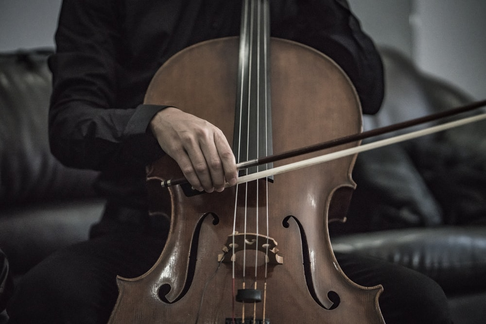 person wearing black dress shirt playing brown cello string instrument