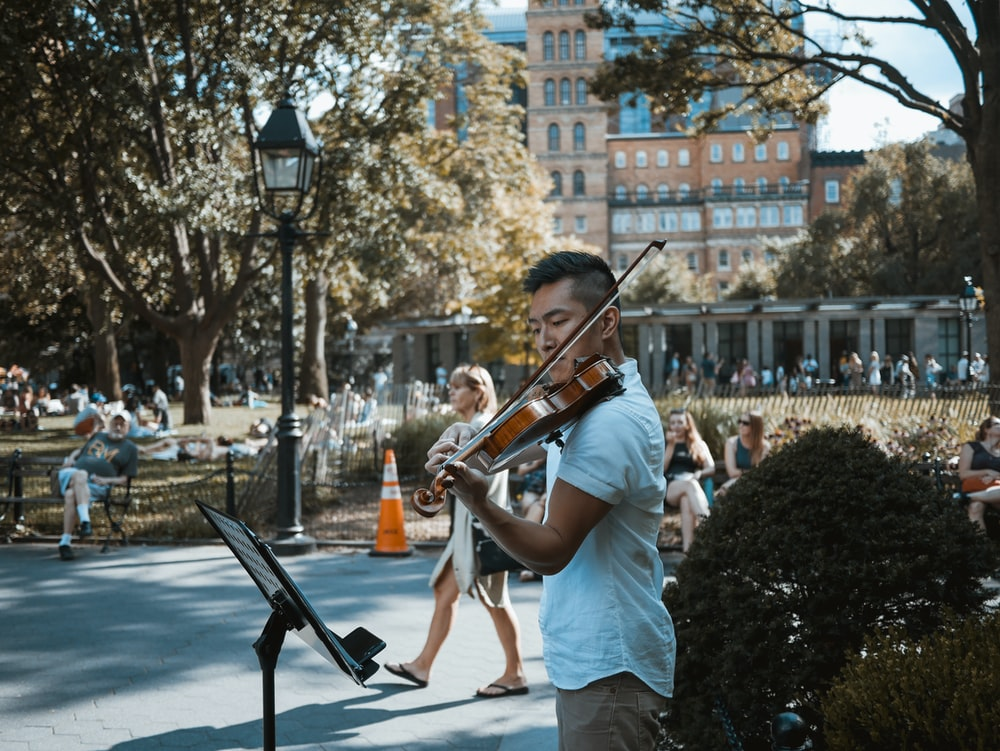 man playing violin at the park