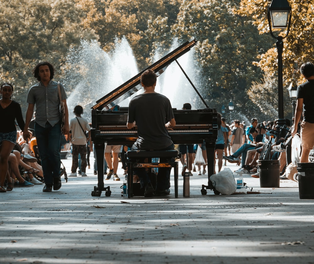 selective focus photography of man playing grand piano in crowd