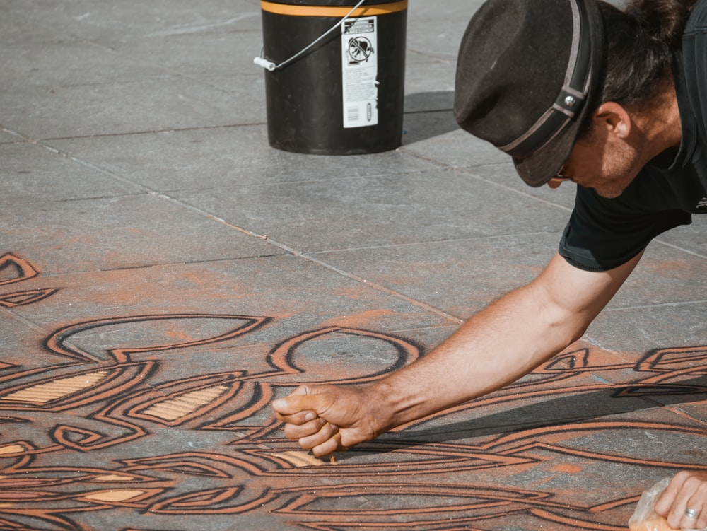 man making sand artwork on the floor