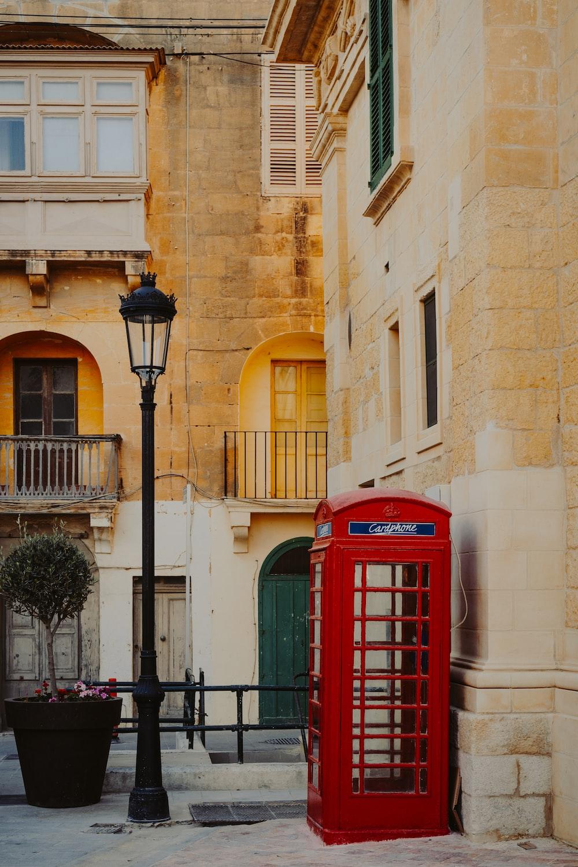 red telephone booth near lantern