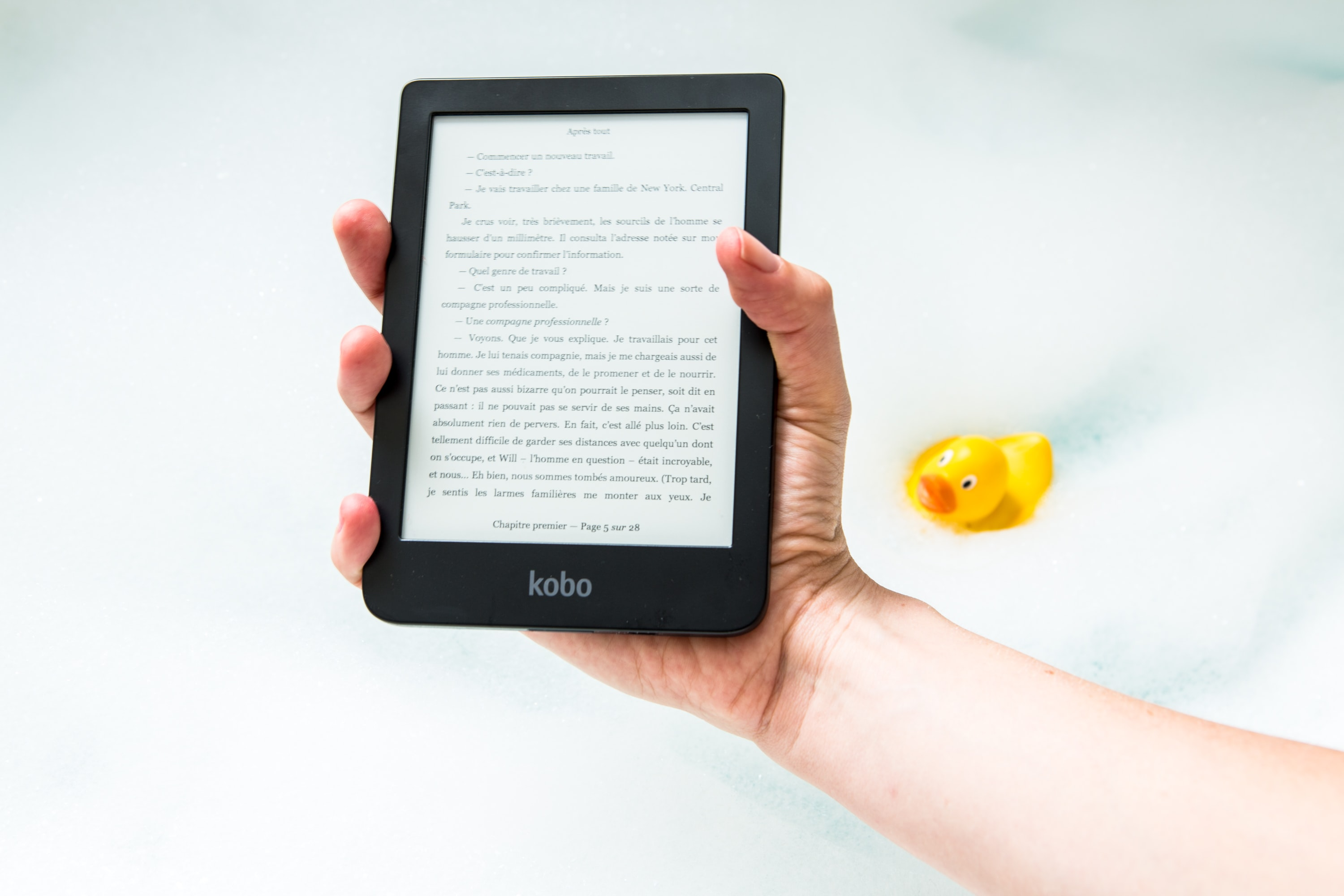 person holding turned on Amazon Kindle ebook reader