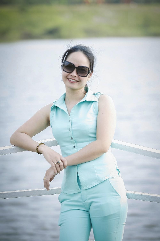 smiling woman wearing collared shirt leaning on white railing