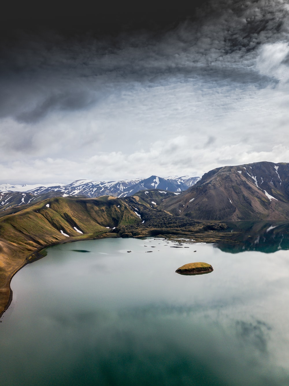 white clouds over body of water and green mountains
