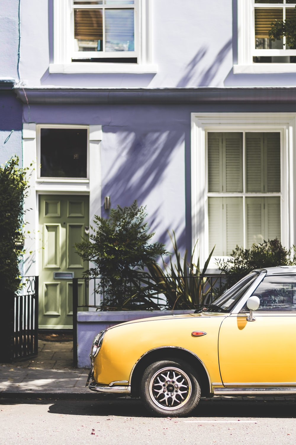 yellow car parked outside house