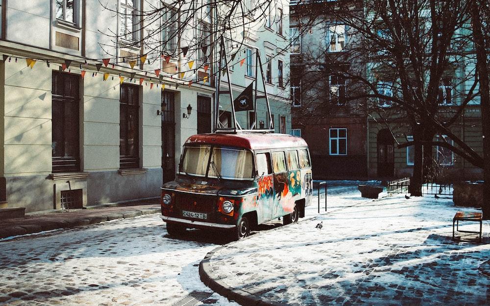 black and multicolored van beside building