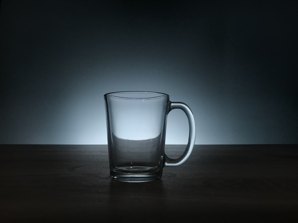 clear glass mug on brown wooden surface
