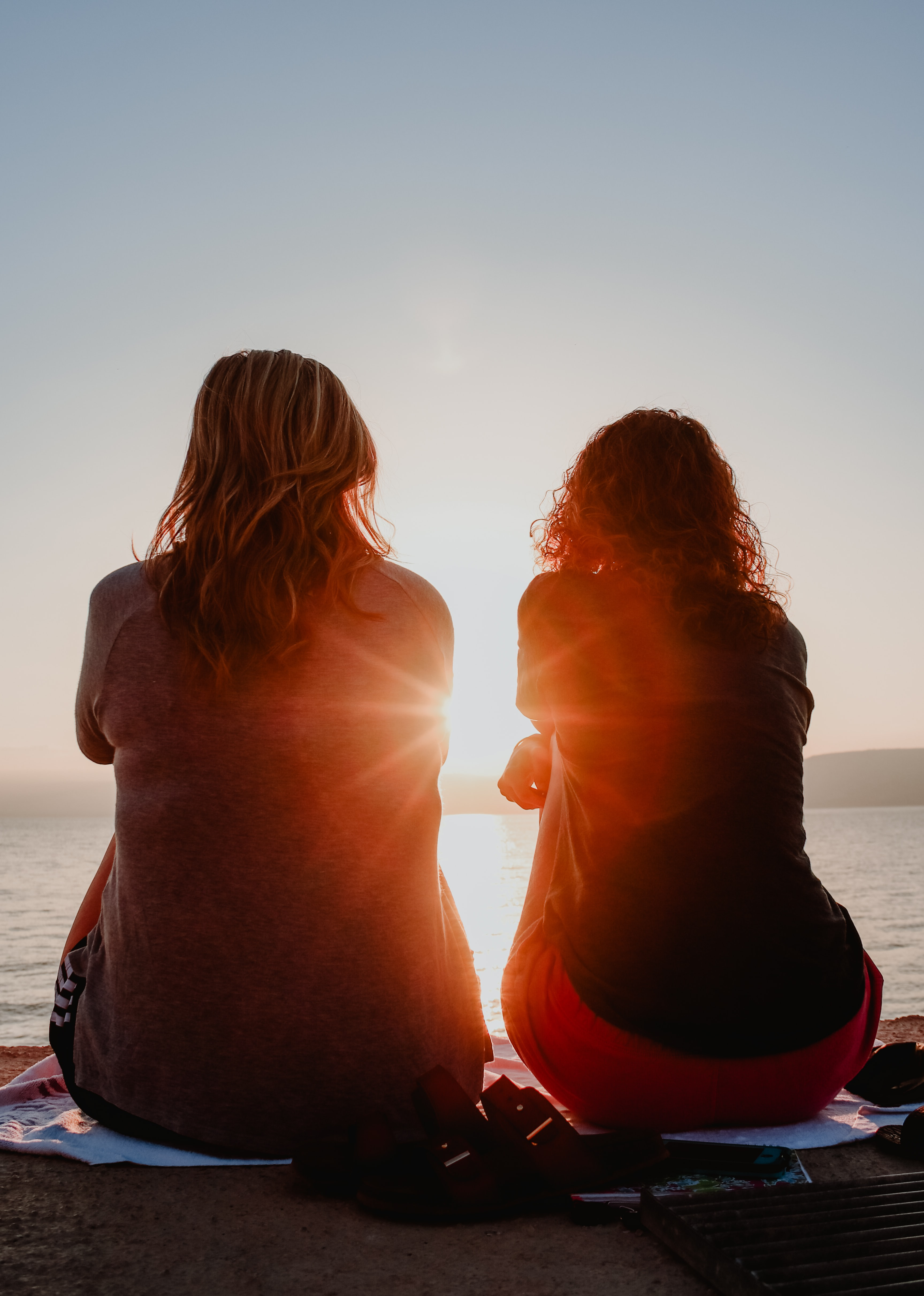 two woman sitting on beach sand while facing sunlight