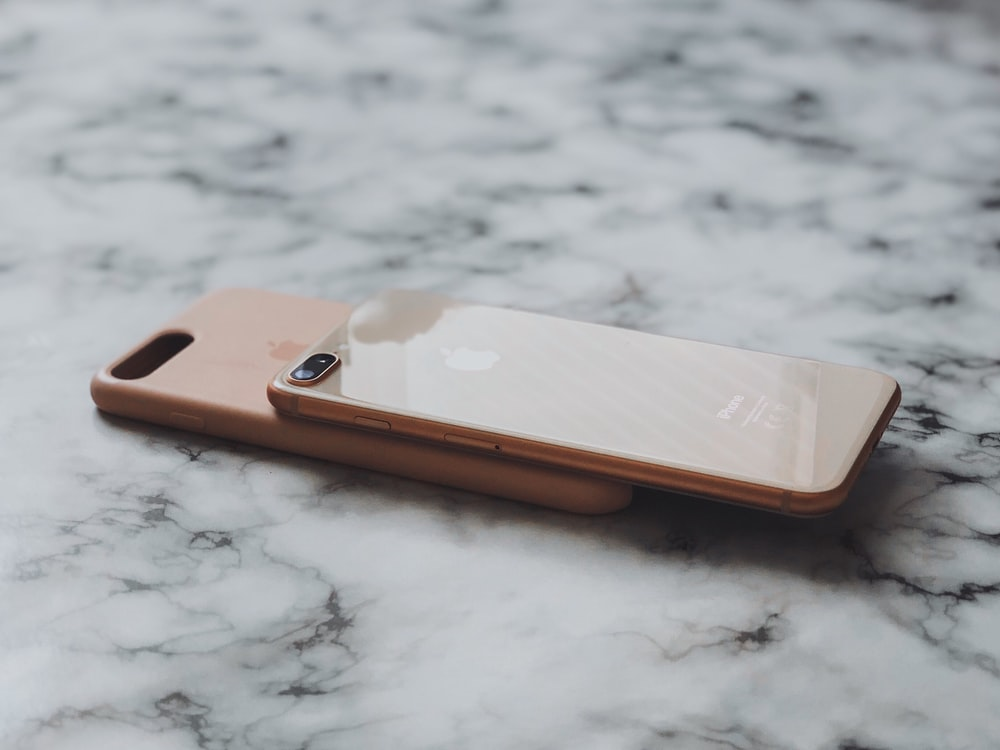 two gold iPhone's on brown surface