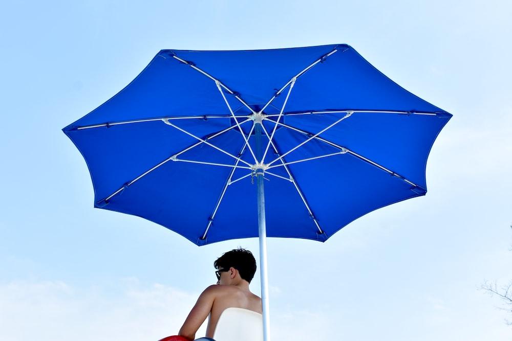 man sitting on chair under blue parasol
