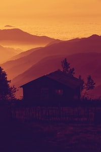 silhouette of brown house near mountains