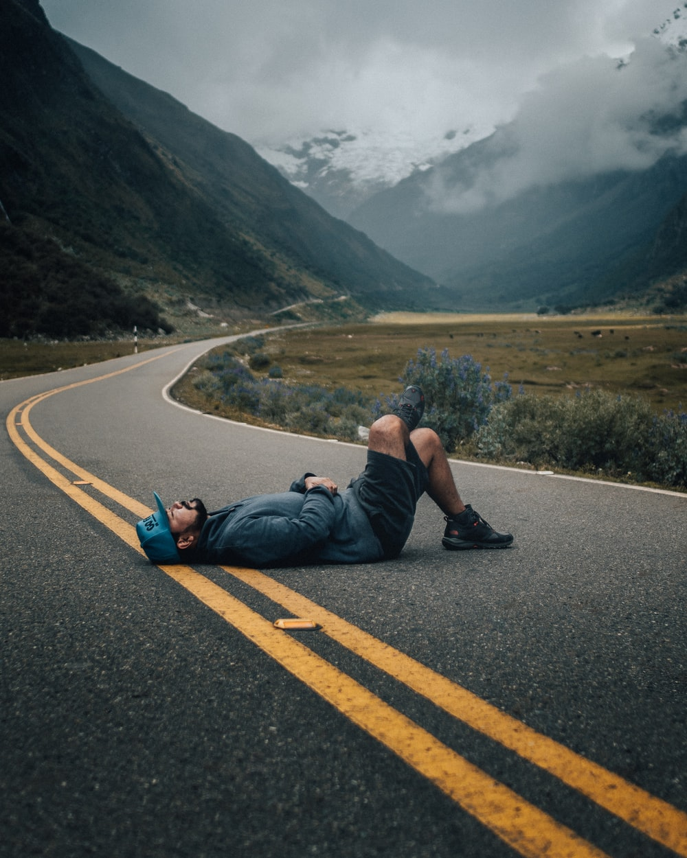 man lying on black concrete top road near green leafed plants