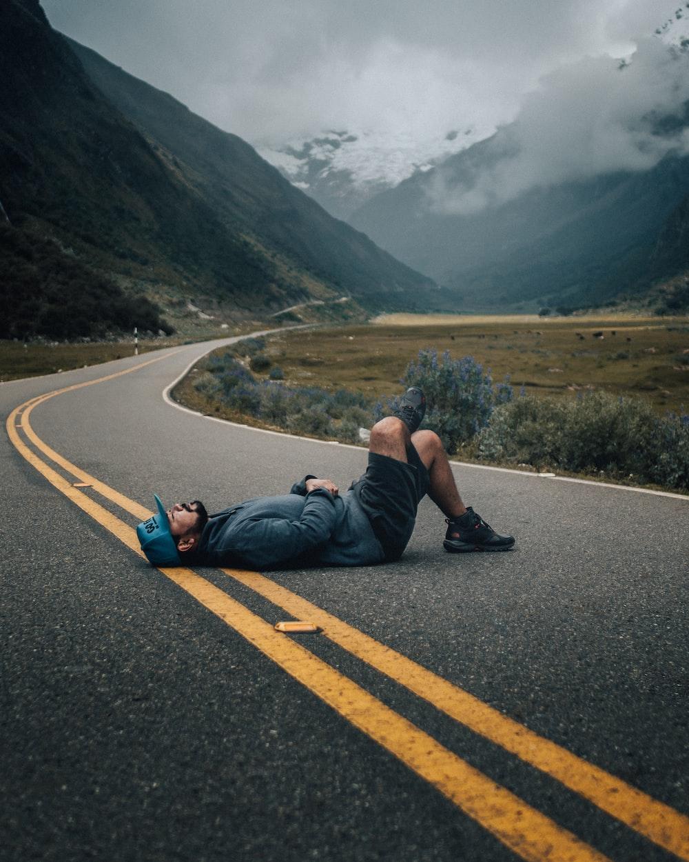 man lying on black concrete top road near green leafed plants