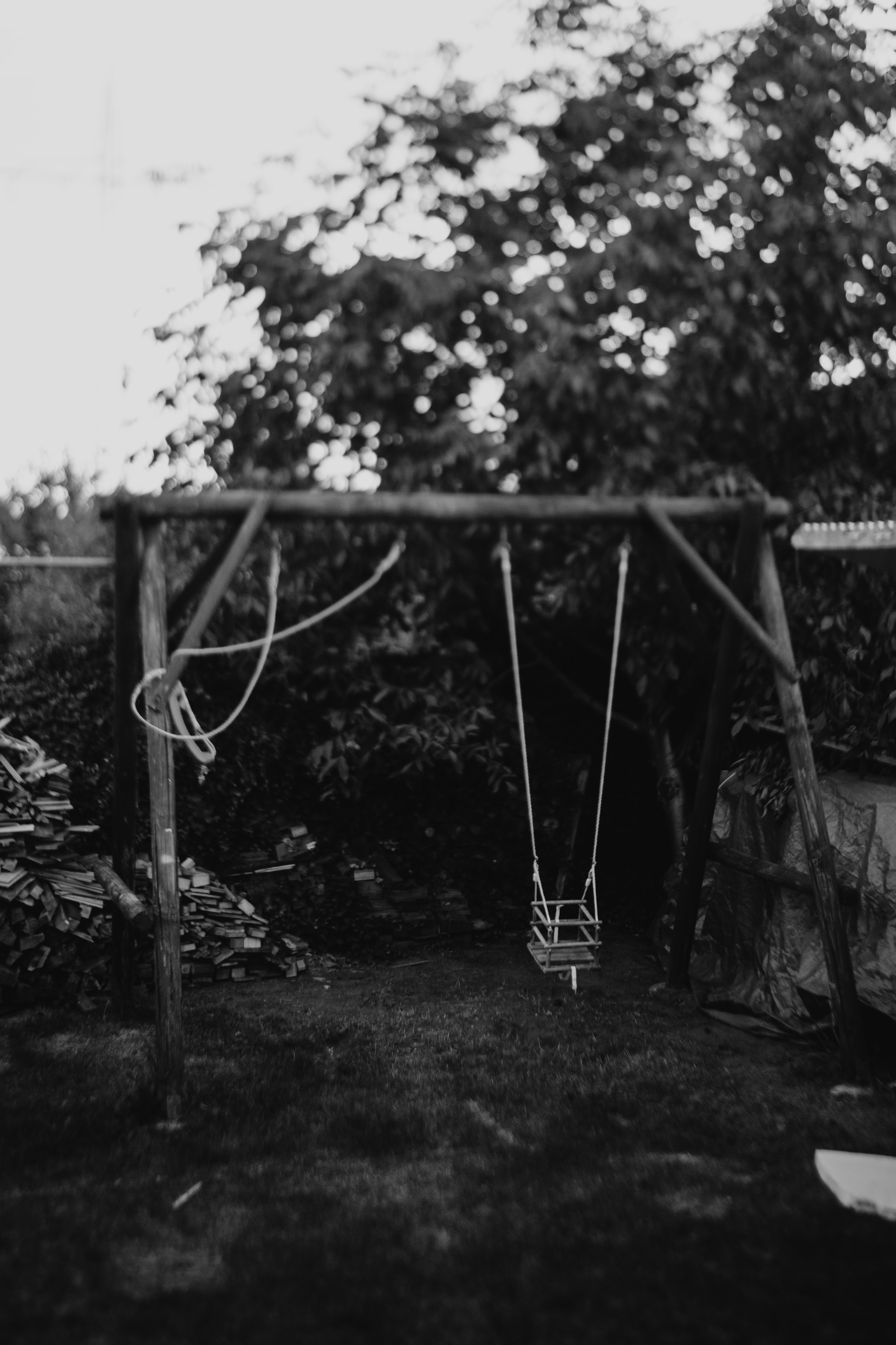 grayscale photo of swing at the garden