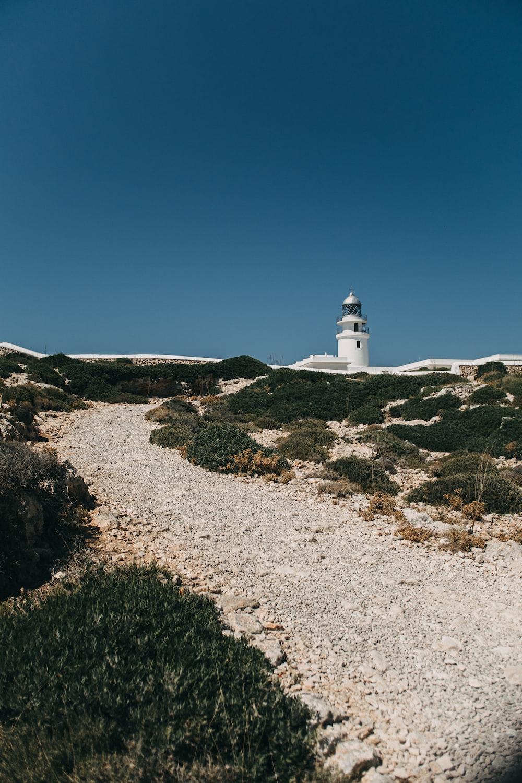 white concrete lighthouse under blue skies