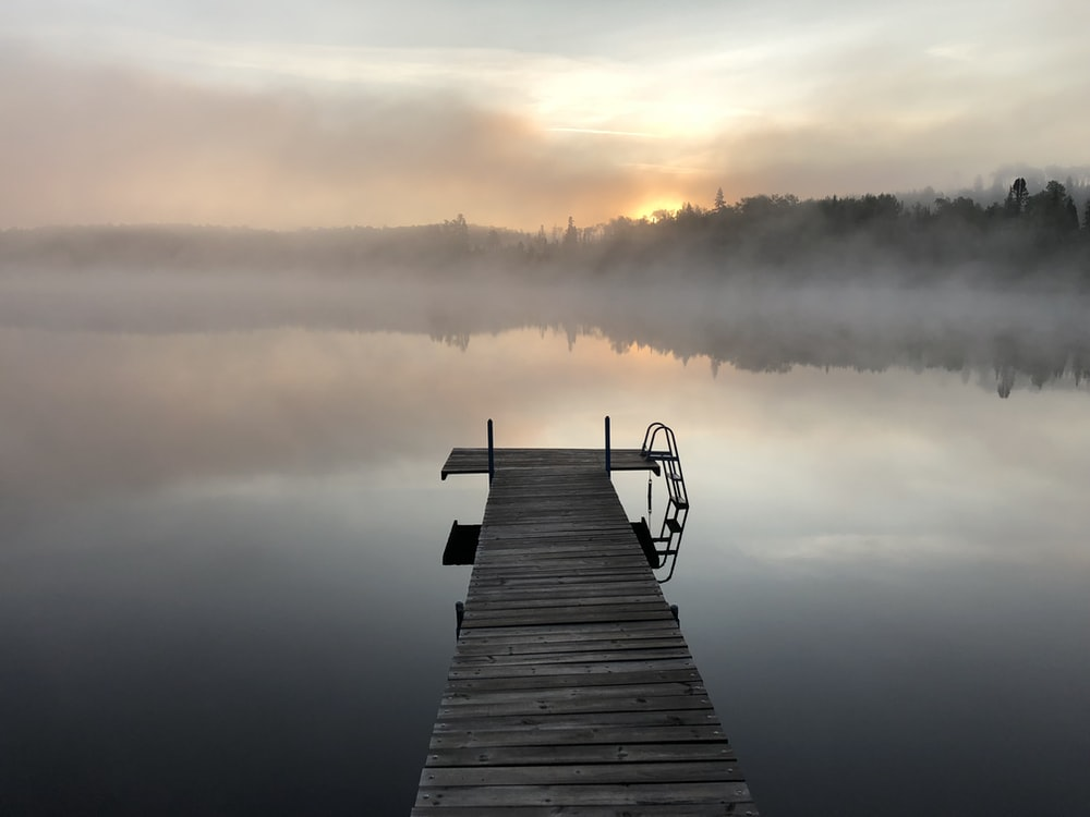 gray wooden pallet sea dock with fog