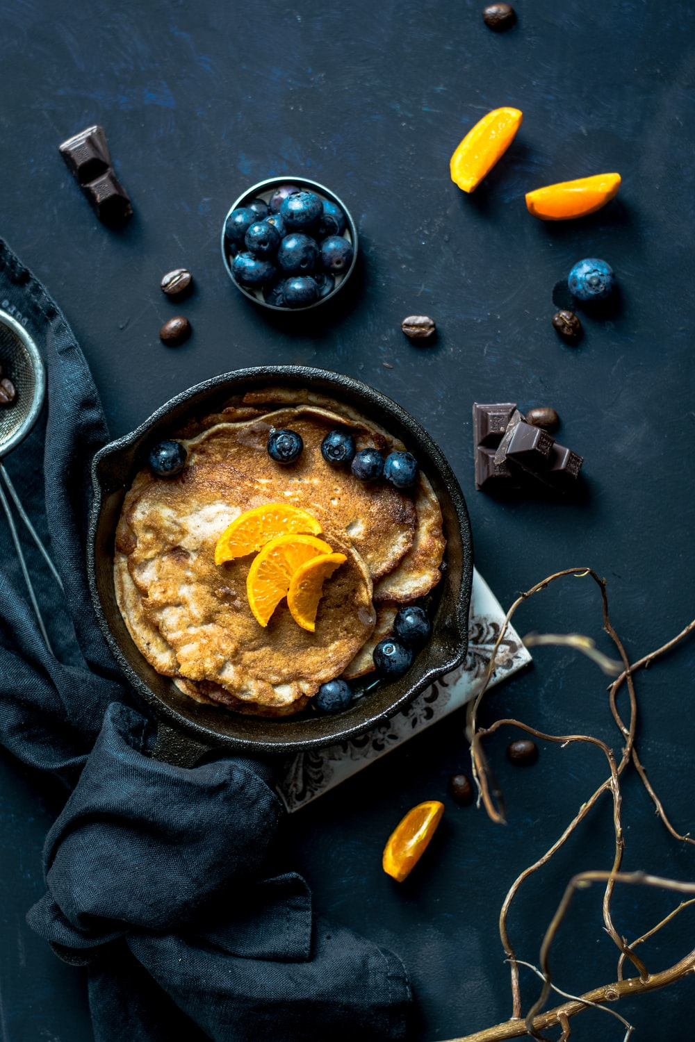 pancake with orange and blueberries beside scattered chocolate and coffee beans