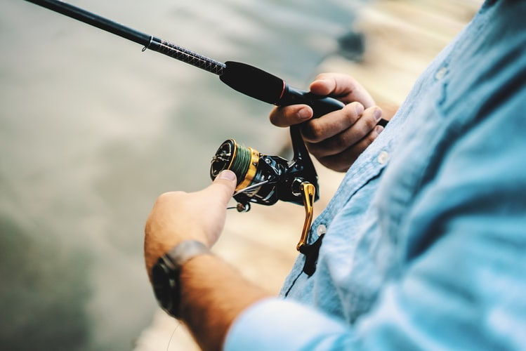 a man fixing the steering wheel of his fishing rod