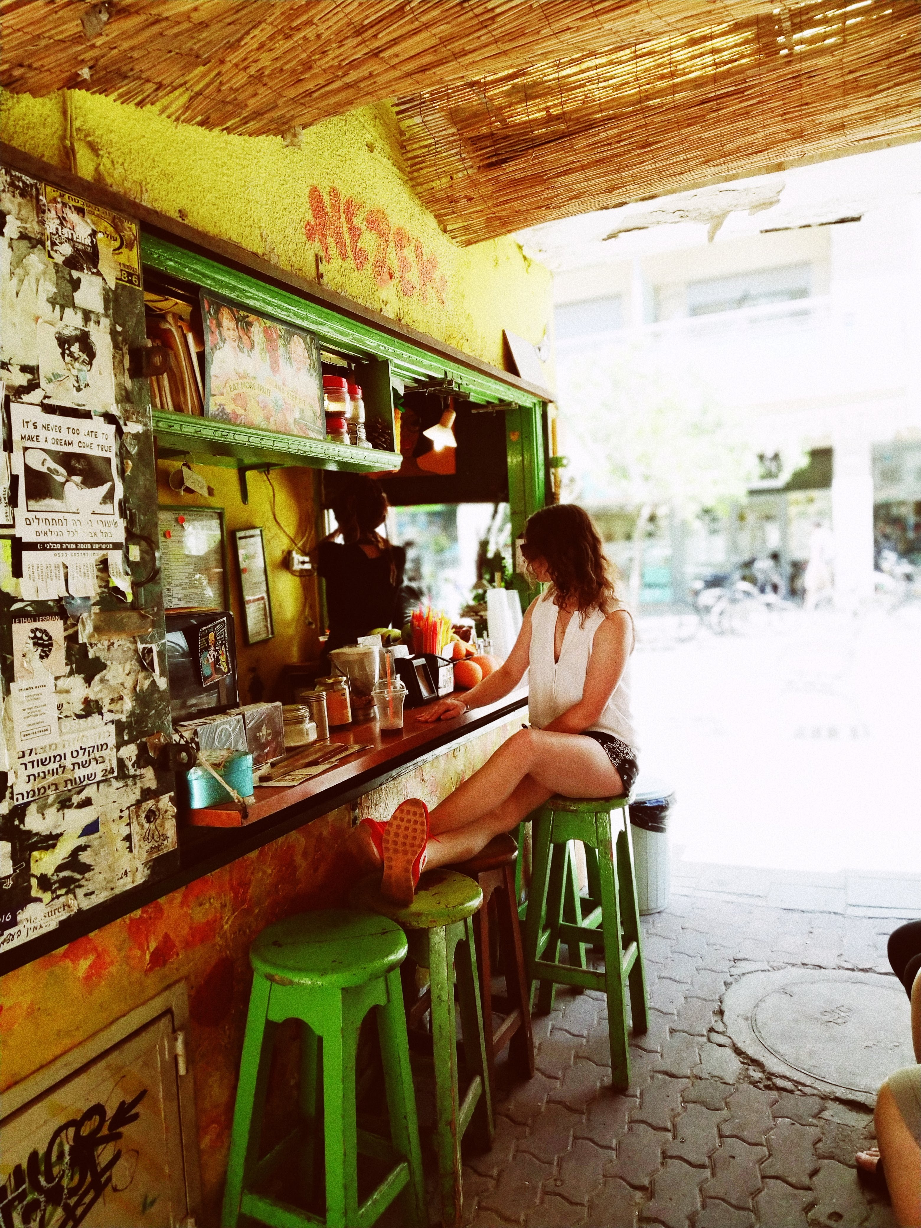 woman sitting on stools near bar counter during daytime