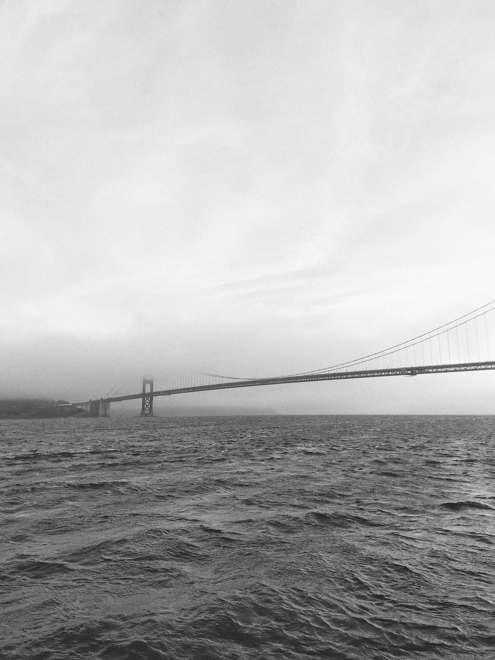 grayscale photo of bridge near body of water