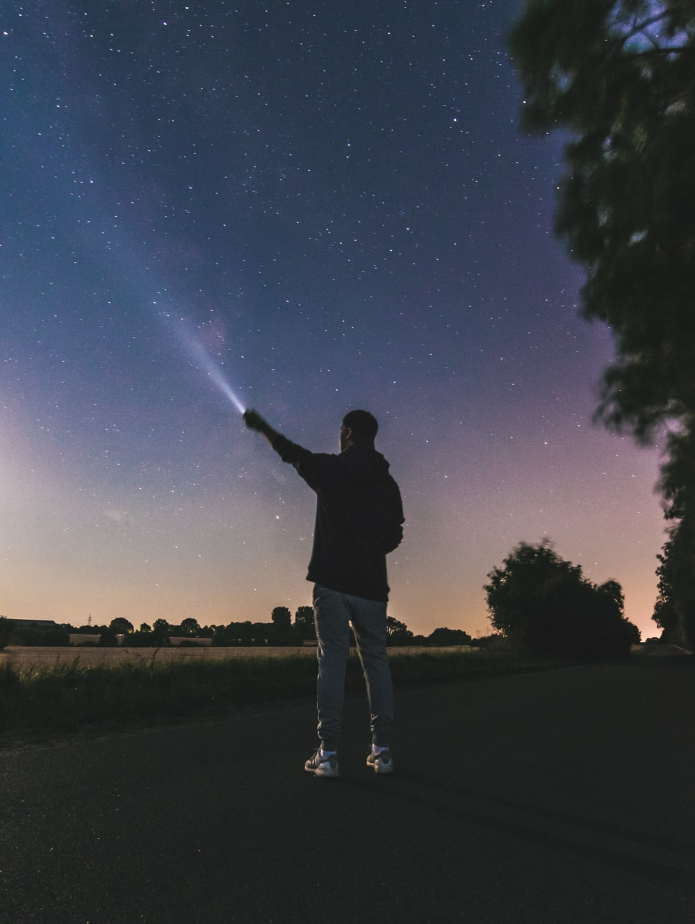 force photography standing man using flashlight at star