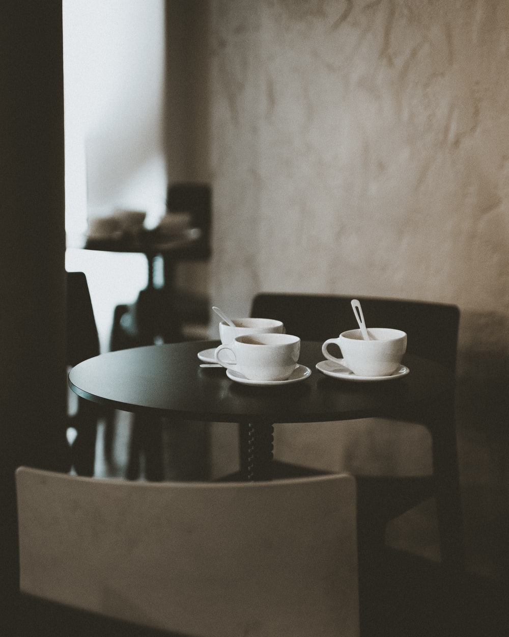 three white ceramic teacups on black wooden table