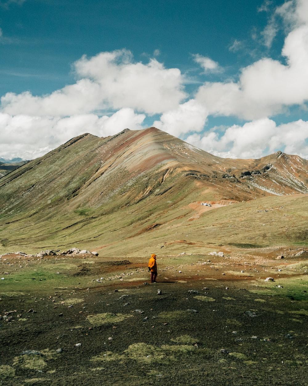 man standing on green grass field near mountain ridge