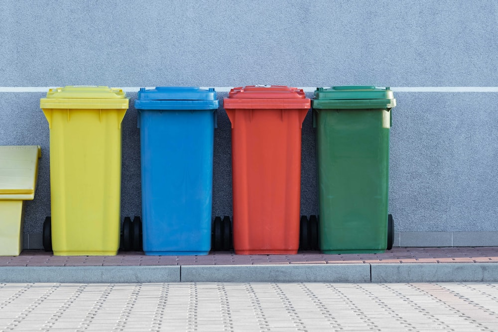 four assorted-color trash bins beside gray wall