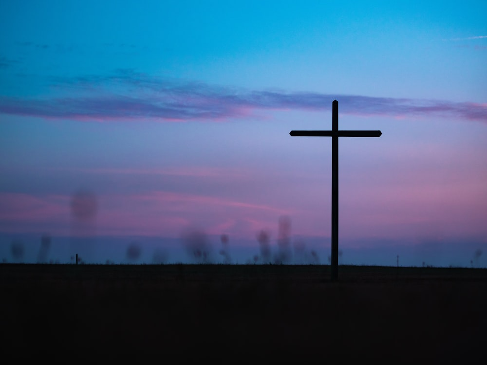 cross stand under purple and blue sky
