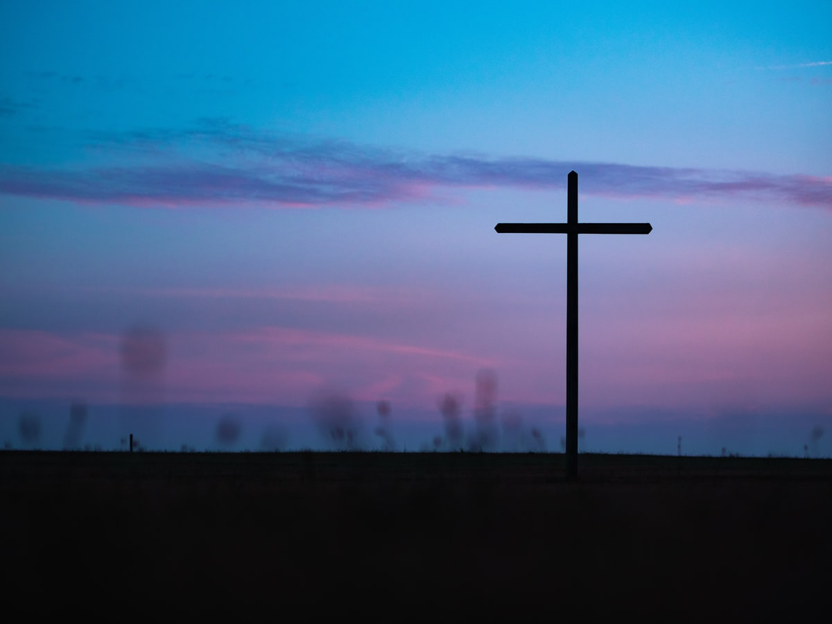 a cross under purple and blue skies
