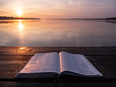 book on top of table and body of water bible teams background