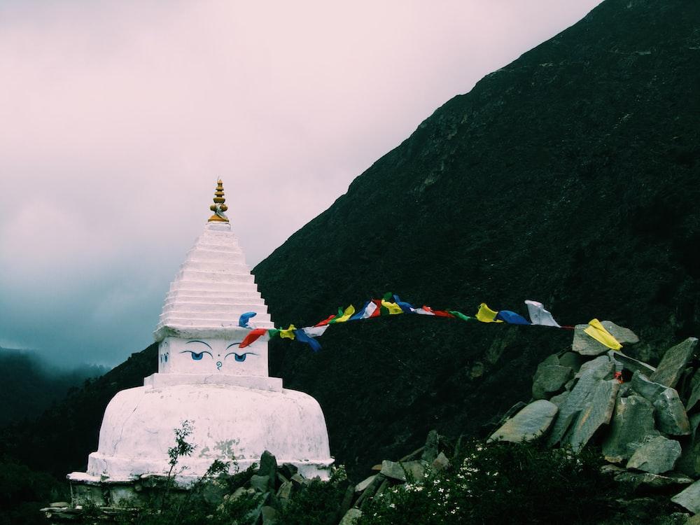 white concrete temple near mountain under white sky
