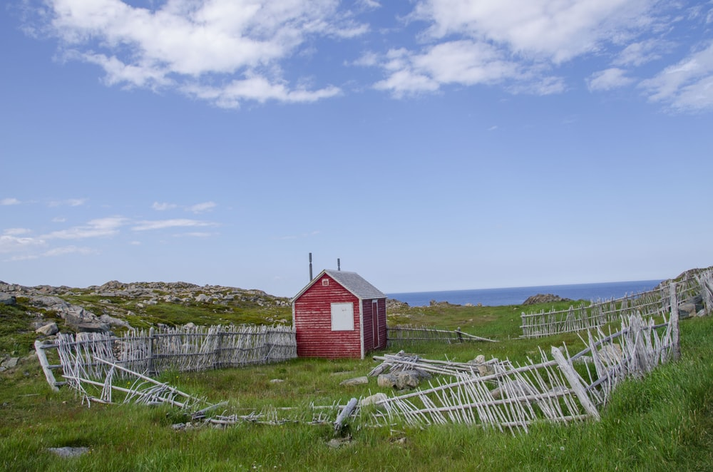 red shed with wrecked fences under blue sky and white clouds during daytime