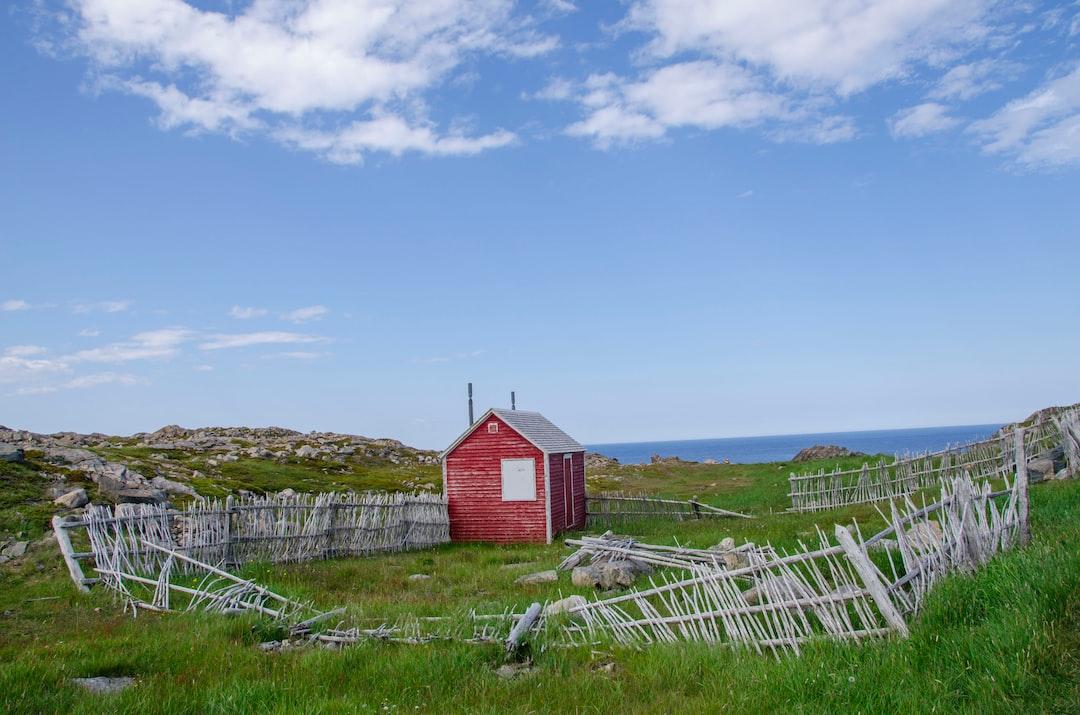 Красный сарай с разбитых заборов под голубым небом и белыми облаками в дневное время