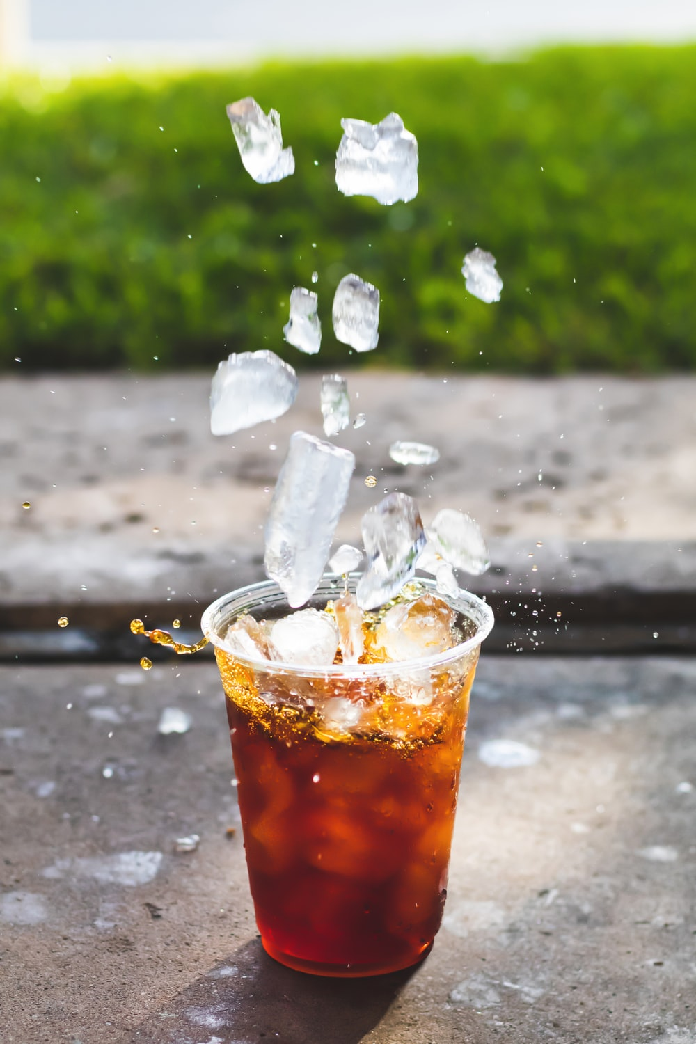 macro photography of dropping ice cube in cup