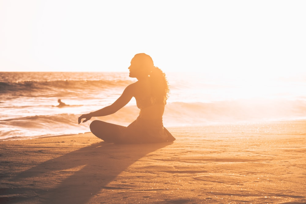 silhouette of woman sitting by the seashore during sunset